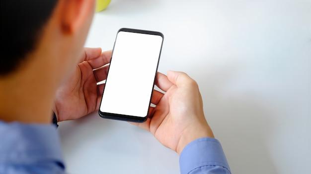 Mann, der smartphonemodell mit leerem schirm verwendet.
