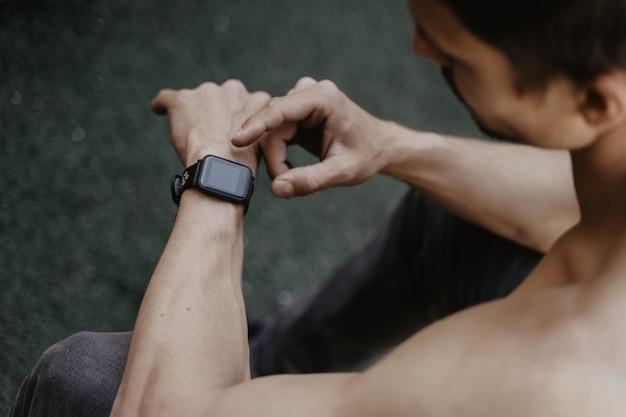 Mann, der smartwatch verwendet, während training ausruht