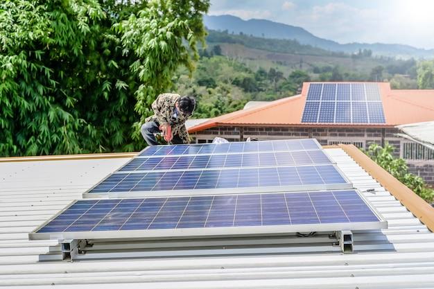 Mann, der sonnenkollektoren auf einem dachhaus für photovoltaik-sichere energie der alternativen energie installiert.