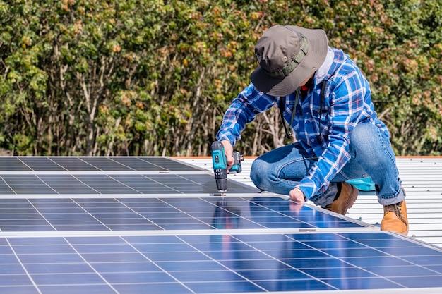 Mann, der sonnenkollektoren auf einem hausdach für photovoltaik-sichere energie der alternativen energie installiert