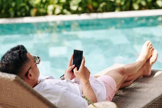 Mann, der sonnigen tag durch schwimmbad verbringt und mobile anwendung oder das überprüfen der sozialen medien auf smartphone verwendet