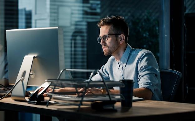 Mann, der spät in der nacht im büro arbeitet