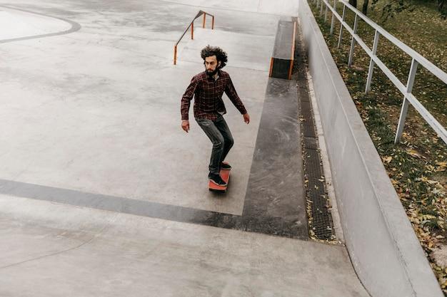 Mann, der spaß mit skateboard draußen hat