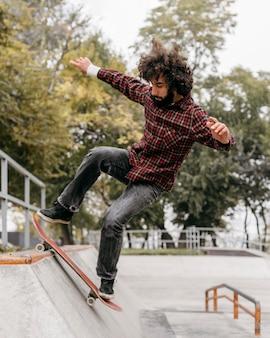 Mann, der spaß mit skateboard im stadtpark hat