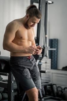 Mann, der sportbekleidung sms am telefon im fitnessstudio trägt