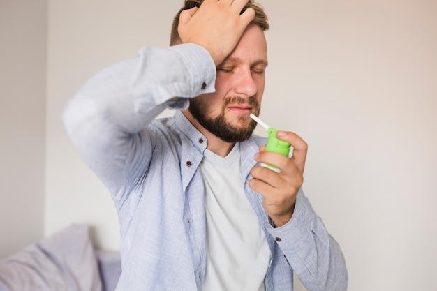 Mann, der spray für halsschmerzen verwendet