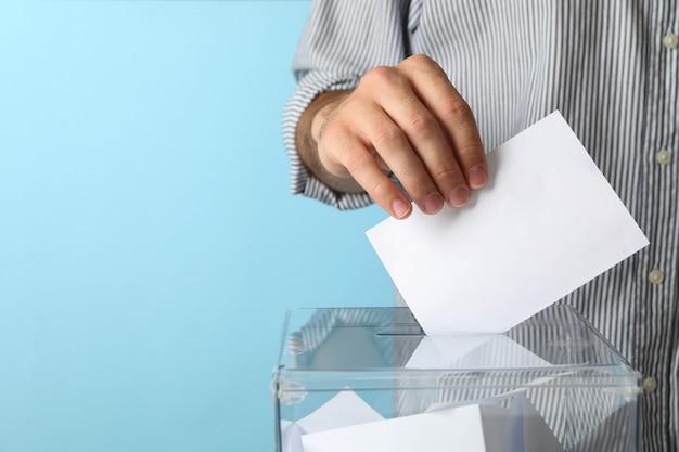 Mann, der stimmzettel in wahlurne setzt
