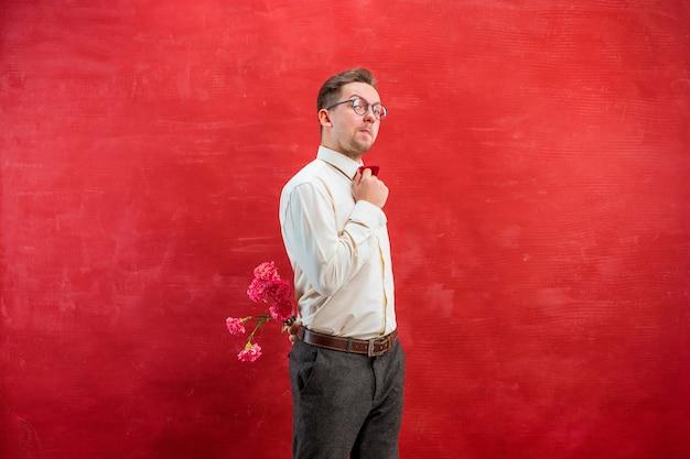 Mann, der strauß der nelken hinter dem rücken auf rotem studiohintergrund hält