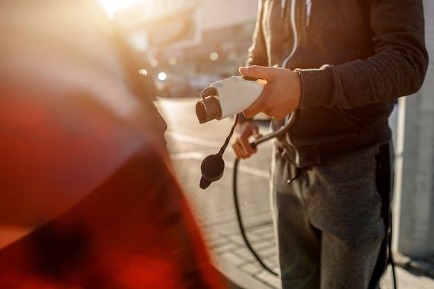 Mann, der stromladekabel für elektroauto im außenparkplatz hält. und er wird das auto mit der ladestation auf dem parkplatz in der nähe des einkaufszentrums verbinden