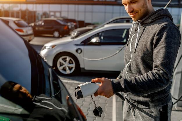 Mann, der stromladekabel für elektroauto im außenparkplatz hält
