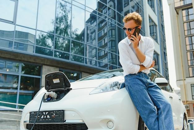 Mann, der stromladekabel für elektroauto im parkplatz im freien hält. und er wird das auto an die ladestation auf dem parkplatz in der nähe des einkaufszentrums anschließen