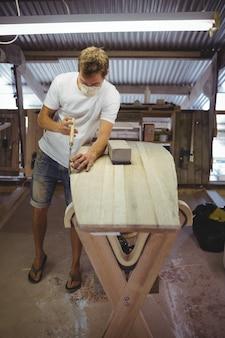 Mann, der surfbrett macht