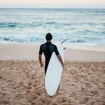 Mann, der surferkleidung trägt, die von hinten auf dem sand geht