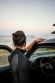 Mann, der surferkleidung von hinten schuss trägt
