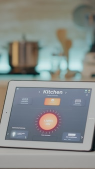 Mann, der tablet mit drahtloser beleuchtungsautomatisierungssoftware auf küchentisch, haus mit intelligentem system betrachtet und lichter einschaltet. digitales tablet mit high-tech-app zur steuerung der stromeffizienz
