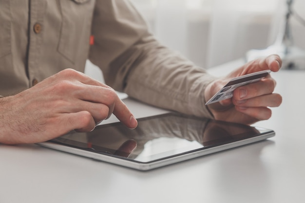 Mann, der tablet-pc und kreditkarte am tisch hält und online einkauft.