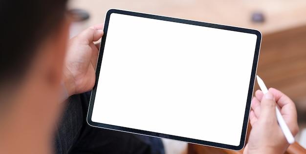 Mann, der tablette des leeren bildschirms im bequemen raum verwendet