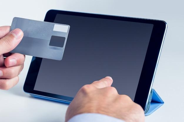 Mann, der tablette für das on-line-einkaufen verwendet