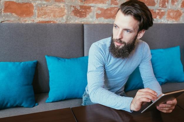 Mann, der tablette hält. mobilität und online-internetzugang über digitale geräte.