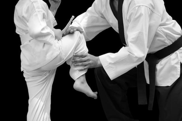 Mann, der taekwondo-kämpfer-kinderbalancen-stand für flug auf schwarzem hintergrund unterrichtet