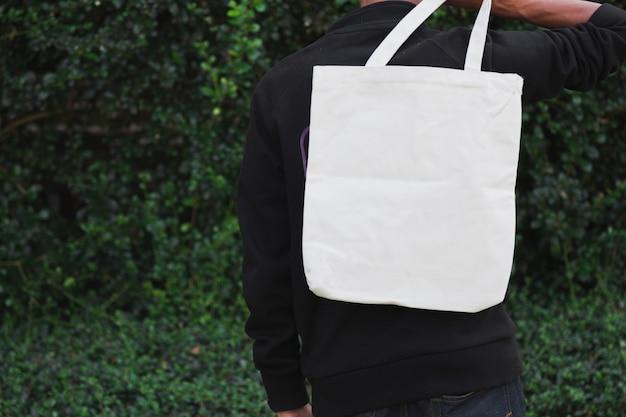 Mann, der tasche leinwand stoff für modell, ökologie-konzept hält.