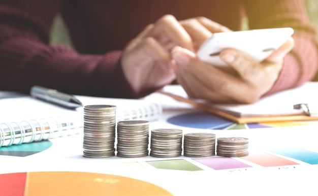 Mann, der taschenrechner mit finanzindizes der börse mit stapelmünze verwendet.