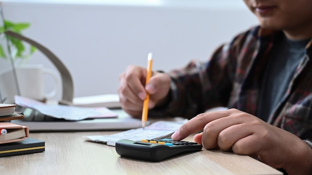 Mann, der taschenrechner verwendet, um rechnungen nach hause zu berechnen.