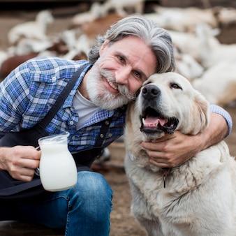 Mann, der tasse ziegenmilch beim spielen mit hund hält