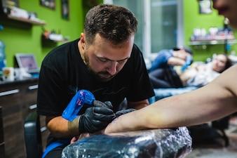 Mann, der Tätowierung auf Arm im Salon macht