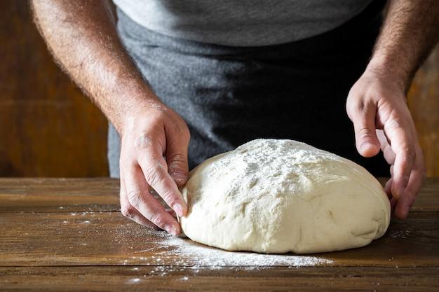 Mann, der teig für das kochen des selbst gemachten brotes zubereitet