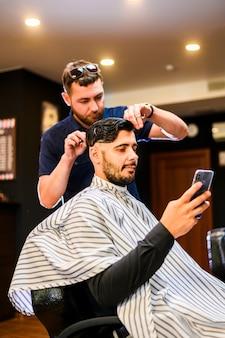 Mann, der telefon beim erhalten eines haarschnitts überprüft