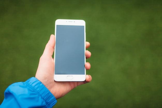 Mann, der telefon in der hand hält, auf einem hintergrund des grünen fußballfeldes.