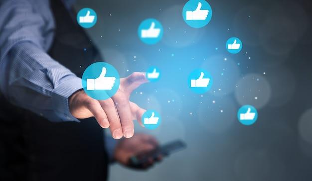 Mann, der telefon mit symbol soziale medien und soziales netzwerk hält. online-marketing-konzept