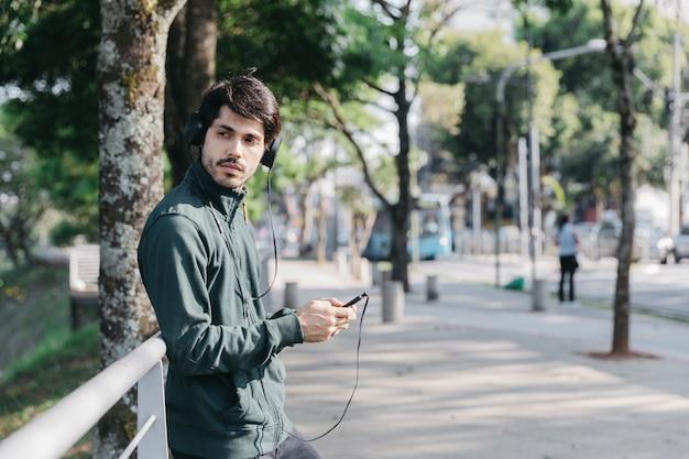 Mann, der telefon verwendet und musik hört
