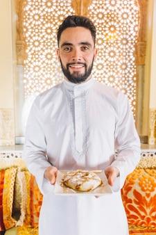 Mann, der teller des arabischen lebensmittels hält