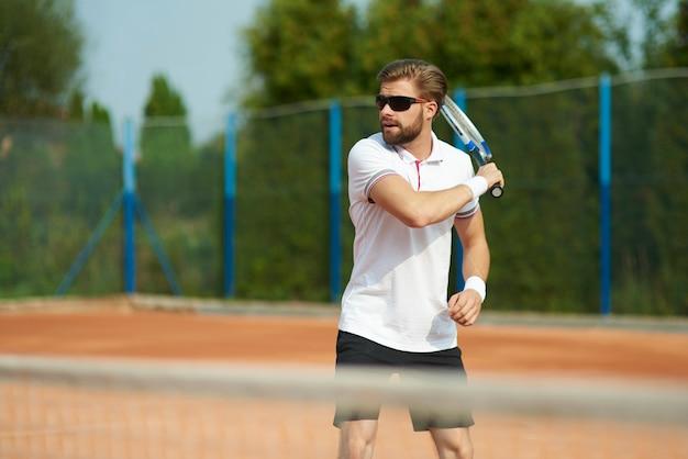 Mann, der tennis an sonnigem tag spielt