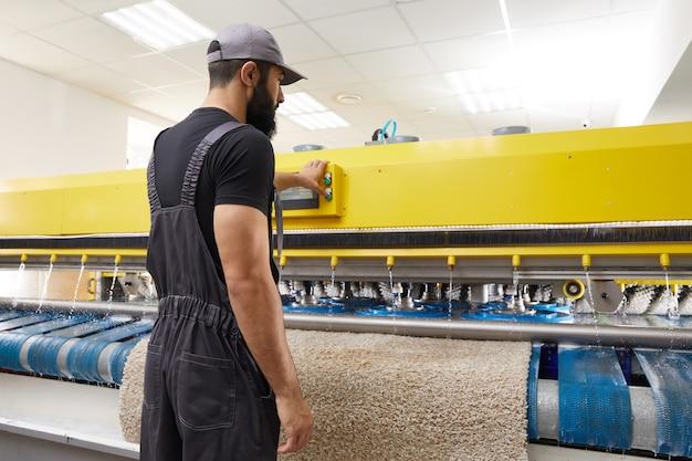 Mann, der teppichautomatische waschmaschine im professionellen wäscheservice betreibt