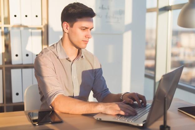 Mann, der text oder blog im büro, hir arbeitsplatz, mit pc-tastatur tippt. busyman arbeitet.