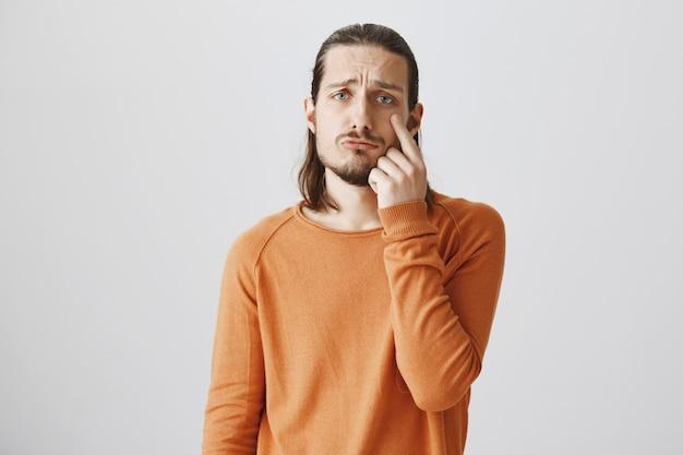Mann, der traurig schaut und träne zeigt