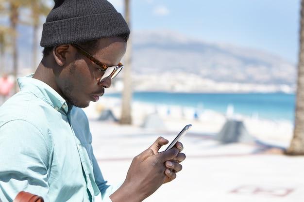 Mann, der trendige kleidung trägt, die schlechte nachrichten unter verwendung eines elektronischen geräts liest