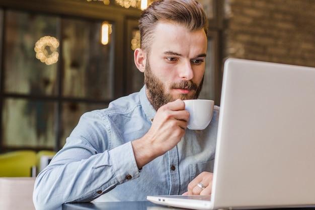 Mann, der trinkenden tasse kaffee des laptops verwendet
