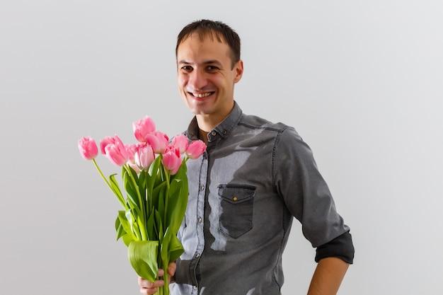 Mann, der tulpen hält. geschenkkartenschablone, poster oder grußkarte - mann mit tulpenstrauß für eine frau. muttertag, valentinstag, konzept zum frauentag. 8. märz geschenk