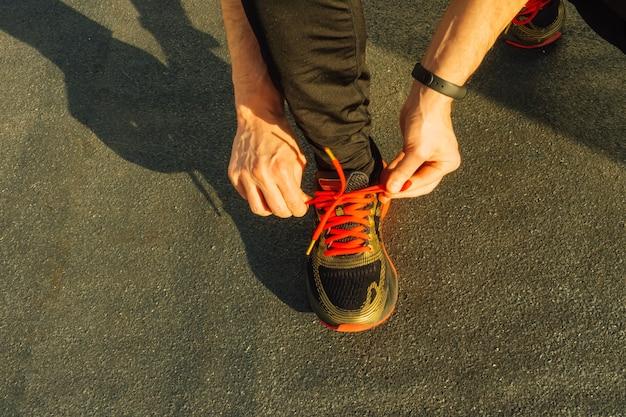 Mann, der turnschuhe auf dem asphalt bindet konzept für sportschuhe.