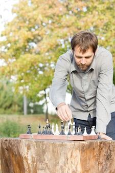 Mann, der über einem schachbrett auf einem rustikalen hölzernen baumstumpf-tisch steht, der schach draußen spielt