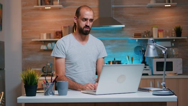 Mann, der über videoanrufe diskutiert, die von zu hause aus arbeiten und in der küche sitzen und auf dem laptop suchen. beschäftigter, fokussierter mitarbeiter, der modernes technologienetzwerk verwendet, um überstunden für das lesen, schreiben und suchen zu machen