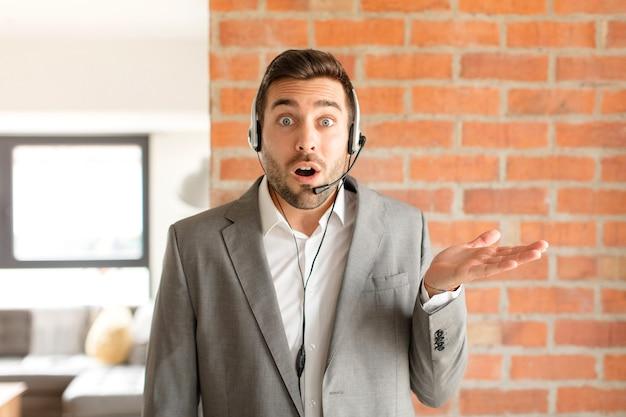 Mann, der überrascht und schockiert aussieht, mit heruntergefallenem kiefer, der einen gegenstand mit einer offenen hand an der seite hält