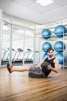 Mann, der übung mit medizinball im studio tut