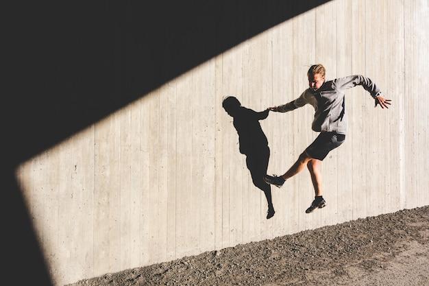 Mann, der übungen tut und auf die wand während des trainings springt