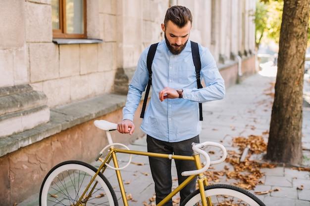 Mann, der uhr nahe fahrrad betrachtet