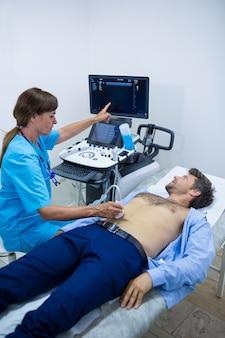 Mann, der ultraschall von einem bauch von arzt